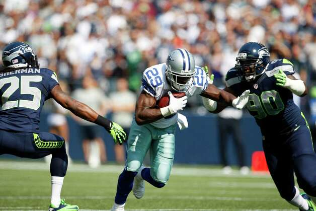 Dallas Cowboys' DeMarco Murray runs between Seattle Seahawks' Richard Sherman, left, and Jason Jones, right in the first half of an NFL football game, Sunday, Sept. 16, 2012, in Seattle. (AP Photo/Kevin P. Casey) Photo: Kevin P. Casey, Associated Press / FR132181 AP