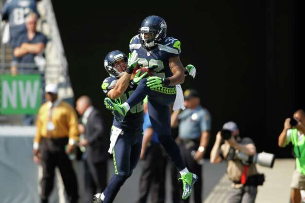 Seattle Seahawks Jeron Johnson (32) leaps in the air and celebrates with Chris Maragos after scoring a touchdown on a blocked kick against the Dallas Cowboys in the first half of an NFL football game, Sunday, Sept. 16, 2012, in Seattle. (AP Photo/John Froschauer) Photo: John Froschauer, Associated Press / FR74207 AP