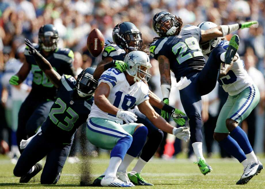 Seattle Seahawks players break up a pass intended for Dallas Cowboys' Miles Austin, center, in the first half of an NFL football game on Sunday, Sept. 16, 2012, in Seattle. Photo: AP