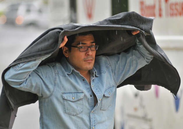 Ricardo Rivero uses his jacket to protect himself from Sunday's rain as he goes into Holy Trinity Church. Photo: Robin Jerstad, For The Express-News / Robert Jerstad   !    !RPO-=