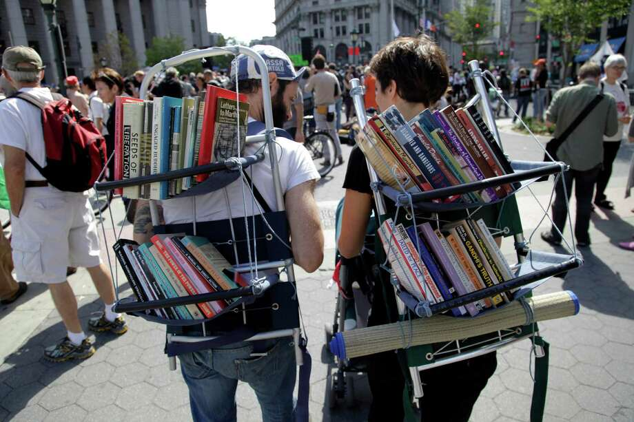 Nathaniel Katz, left, and Valentina Curandi carry a small pacifist library on their backs during an Occupy Wall Street anniversary concert in Foley Square in New York on Sunday, Sept. 16, 2012. The Occupy Wall Street movement will mark its first anniversary on Monday. (AP Photo/Seth Wenig) Photo: Seth Wenig, Associated Press / AP