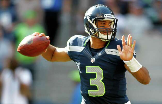 Seattle Seahawks quarterback Russell Wilson drops back to pass against the Dallas Cowboys in the second half of an NFL football game on Sunday, Sept. 16, 2012, in Seattle. (AP Photo/John Froschauer) Photo: John Froschauer, Associated Press / FR74207 AP