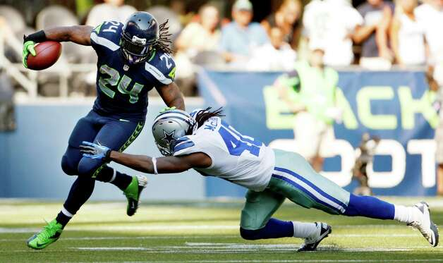Seattle Seahawks' Marshawn Lynch (24) rushes as Dallas Cowboys' Danny McCray tries to tackle during the second half of an NFL football game, Sunday, Sept. 16, 2012, in Seattle. (AP Photo/Kevin P. Casey) Photo: Kevin P. Casey, Associated Press / FR132181 AP