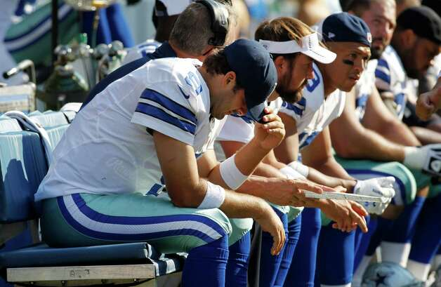 Dallas Cowboys quarterback Tony Romo, left, sits on the bench after being sacked in the second half of an NFL football game against the Seattle Seahawks, Sunday, Sept. 16, 2012, in Seattle. (AP Photo/John Froschauer) Photo: John Froschauer, Associated Press / FR74207 AP
