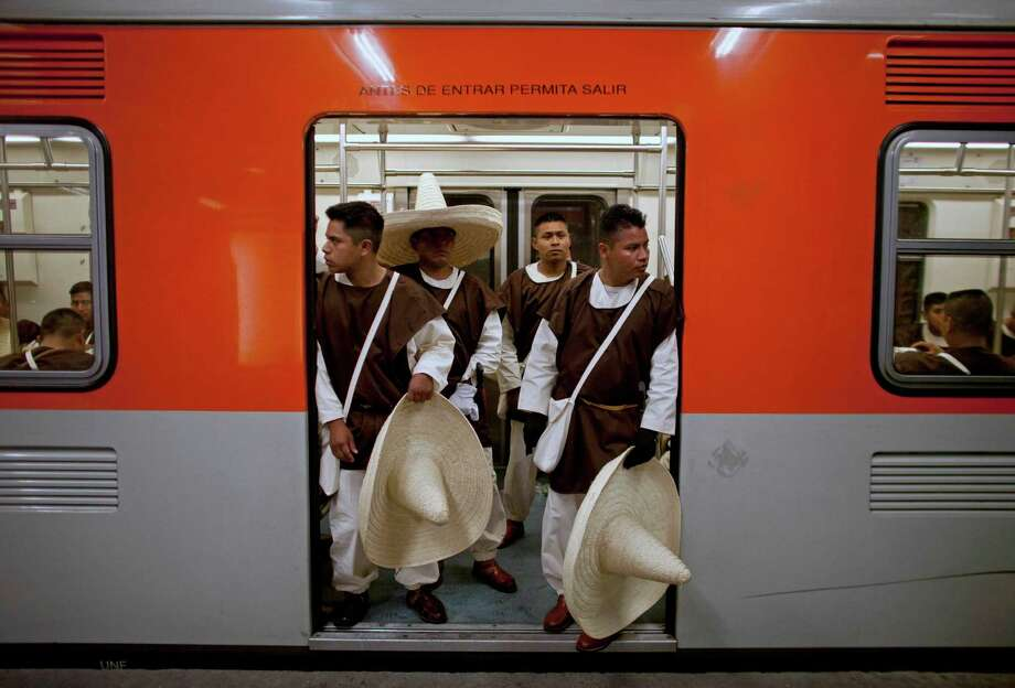 Members of the military, wearing costumes representing the 1911 revolutionary forces, stnad inside a subway train on their way to downtown Mexico City, prior to the military parade of the Independence Day celebrations, Mexico City, Sunday Sept. 16, 2012. Mexico celebrates the 202nd anniversary of its 1810 independence uprising. (AP Photo/Alexandre Meneghini) Photo: Alexandre Meneghini, Associated Press / AP