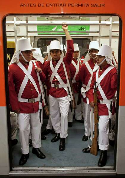 Members of the Mexican army wearing historical uniforms ride in the subway on their way to downtown