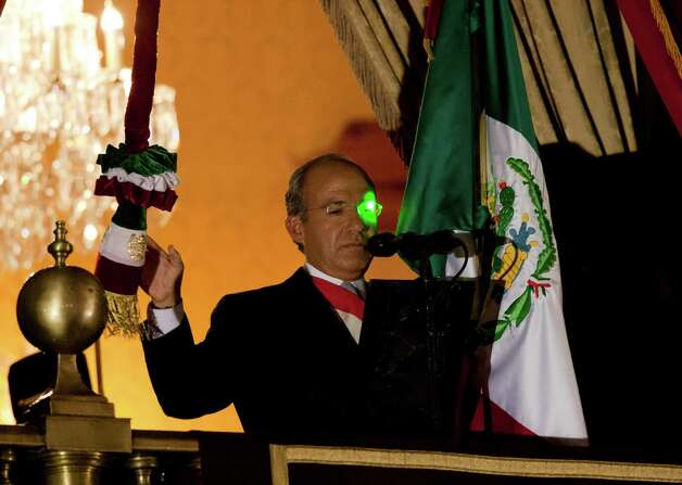 "A green laser light reflects on President Felipe Calderon's face at the balcony of the National Palace during the traditional ""El Grito,"" or shout, to kick off Independence Day celebrations at the Zocalo in Mexico City, late Saturday, Sept. 15, 2012. Mexico is marking the 202st anniversary of the ""Grito de Dolores,"" honoring the call to arms made by the priest Miguel Hidalgo in 1810 that began the struggle for independence from Spain, achieved in 1821. (AP Photo/Eduardo Verdugo) Photo: Eduardo Verdugo, Associated Press / AP"