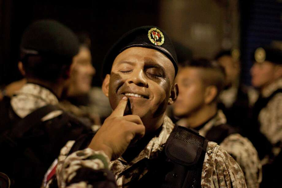 A member of the Mexico's Army Special Forces is helped by a colleague to prepare camouflage makeup on his face prior to the military parade of the Independence Day celebrations, Mexico City, Sunday Sept. 16, 2012.  Photo: Alexandre Meneghini, Associated Press / AP