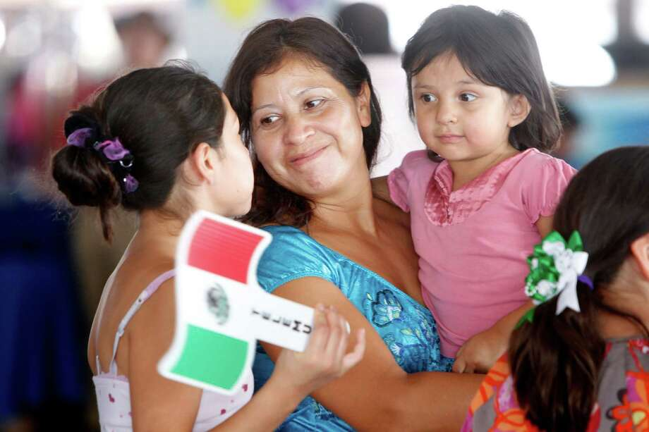 Alma Mendez, 40, carries daughter Bianca Mendez, 2, and talks to daughter Kimberly Mendez, 11, as they wait for the entertainment to begin during the Fiestas Patrias at Traders Village in recognition of Mexican Independence Day on Sunday, Sept. 16, 2012, in Houston. Photo: Mayra Beltran, Houston Chronicle / © 2012 Houston Chronicle