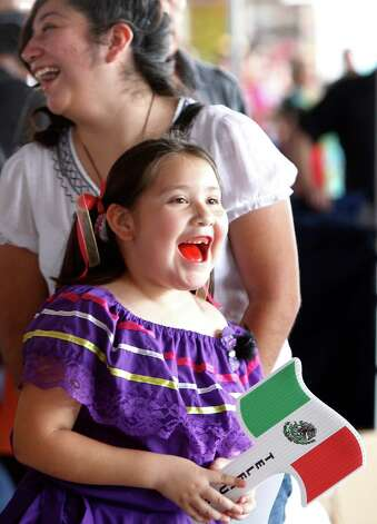 Alexa Vasquez, 6, and sister Sara Vasquez, 15, enjoy the Fiestas Patrias at Traders Village in recognition of Mexican Independence Day on Sunday, Sept. 16, 2012, in Houston. Photo: Mayra Beltran, Houston Chronicle / © 2012 Houston Chronicle