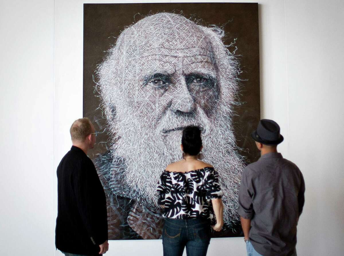 Art enthusiasts look at a painting of Charles Darwin by Alexi Torres, during the Houston Fine Art Fair, Sunday, Sept. 16, 2012, in Reliant Center in Houston.