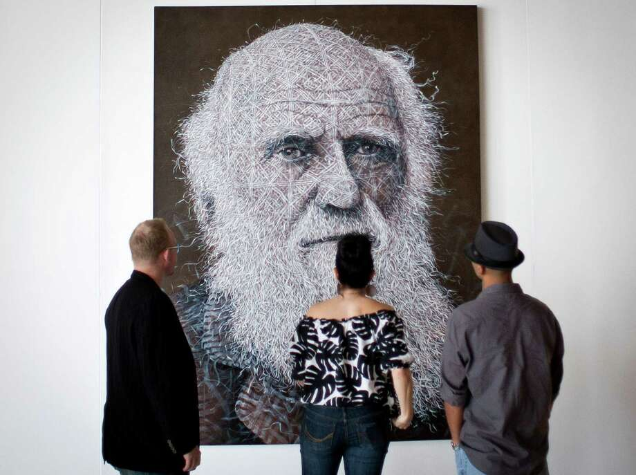 Art enthusiasts look at a painting of Charles Darwin by Alexi Torres, during the Houston Fine Art Fair, Sunday, Sept. 16, 2012, in Reliant Center in Houston. Photo: Nick De La Torre, Houston Chronicle / © 2012 Houston Chronicle