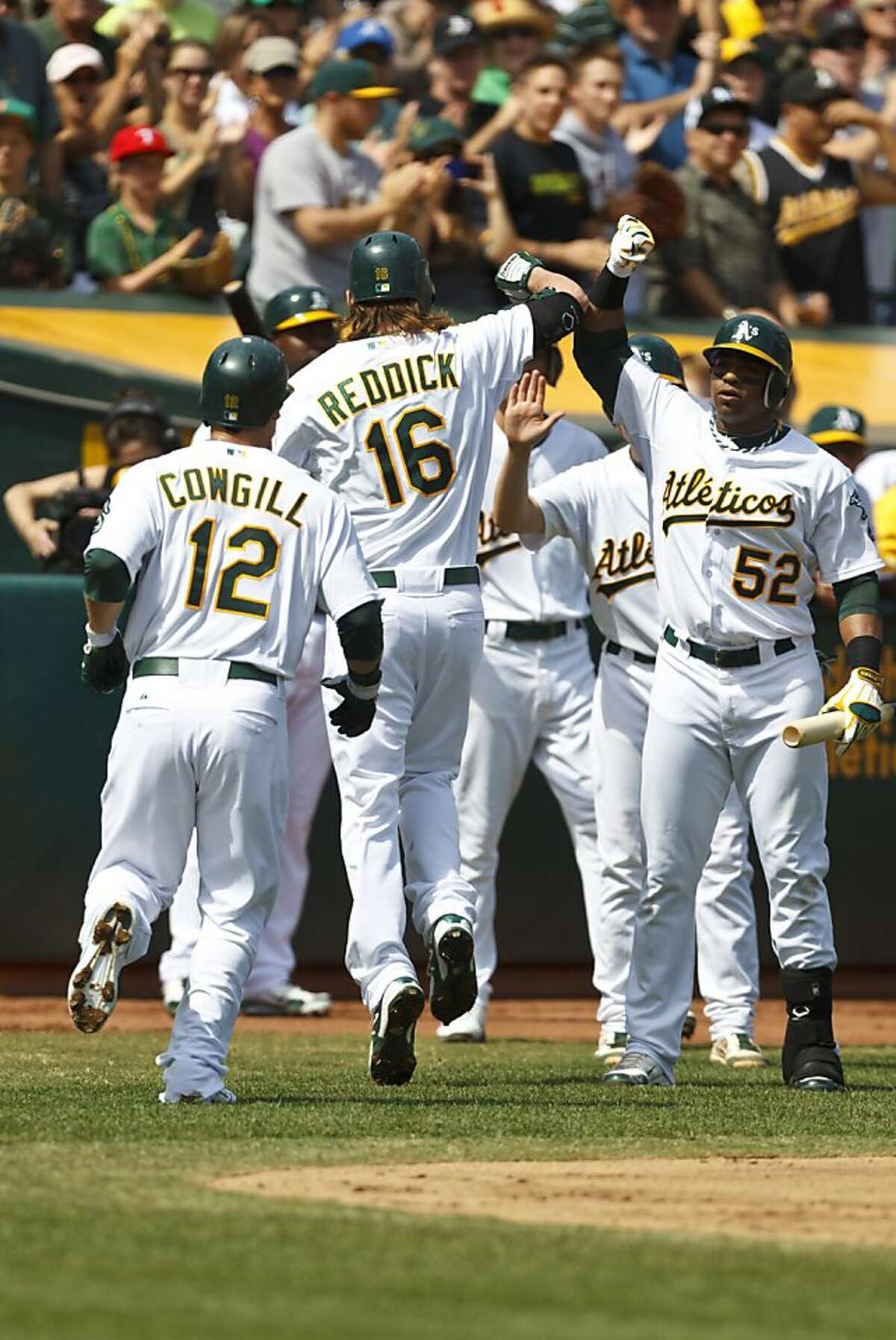 Josh Reddick of the Oakland Athletics is congratulated after hitting a two run home run against the Orioles on Sept. 16th. No one expected a team with a collective .236 batting average and the second-lowest team payroll, the one picked by sportswriters to finish dead last, to put up a fight this season.