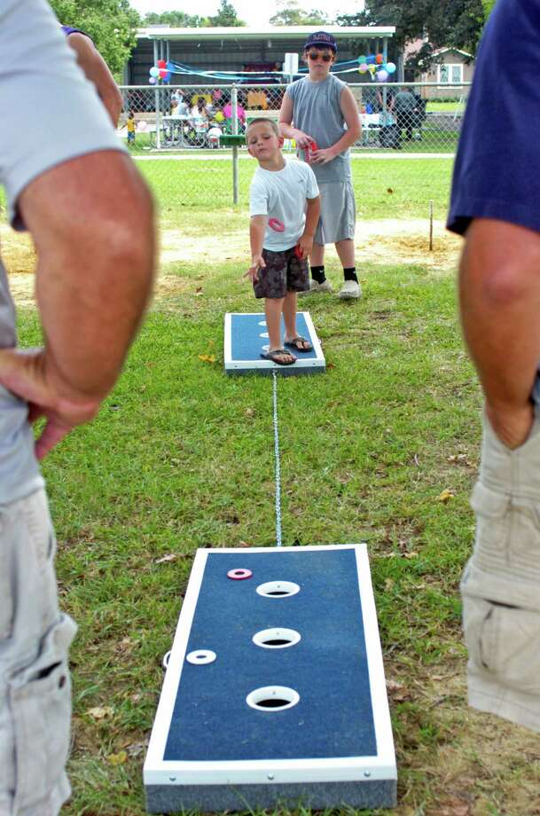 Kooper Benoit, 5, takes his turn while Brian Guthrie, 12, looks on at the Texas Pecan Festival Washer Board Shootout on Sunday at Lion's Park in Groves. The simple (but not easy) game has been gaining in popularity in recent years. Photo: Sarah Moore