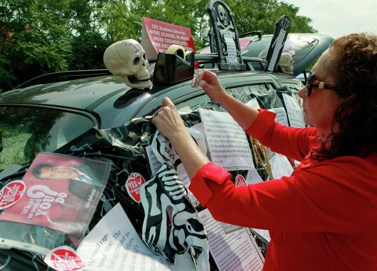 Philomena Johnson, a delegate from Little Village Academy, decorates her vehicle on Sunday to highlight the need for increased social services in Chicago schools. Classes are cancelled Monday for 350,000 students.