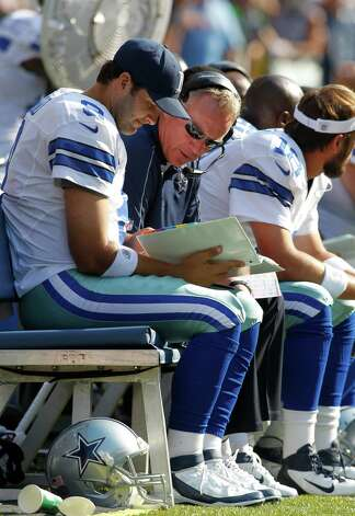 Dallas Cowboys quarterback Tony Romo holds a playbook while talking with a coach on the bench against the Seattle Seahawks in the second half of an NFL football game, Sunday, Sept. 16, 2012, in Seattle. (AP Photo/John Froschauer) Photo: John Froschauer, Associated Press / FR74207 AP