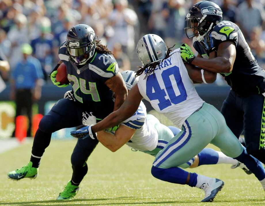 Seattle Seahawks' Marshawn Lynch is hit by Dallas Cowboys' Dan Connor, rear, and Danny McCray as Seahawks' Anthony McCoy blocks in the second half of an NFL football game, Sunday, Sept. 16, 2012, in Seattle. (AP Photo/John Froschauer) Photo: John Froschauer, Associated Press / FR74207 AP