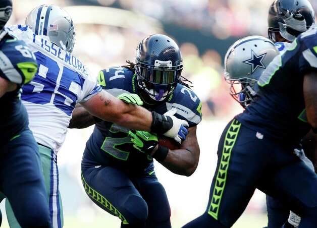 CORRECTS TO RUNS FOR YARDAGE NOT SCORES - Seattle Seahawks' Marshawn Lynch (24) pushes aside Dallas Cowboys' Sean Lissemore as he runs for yardage in the second half of an NFL football game of Sunday, Sept. 16, 2012, in Seattle. (AP Photo/Kevin P. Casey) Photo: Kevin P. Casey, Associated Press / FR132181 AP