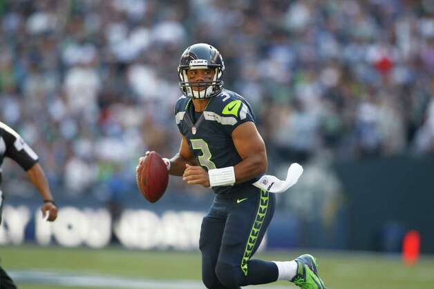 Seattle Seahawks quarterback Russell Wilson rolls out to look for an open reciever against the Dallas Cowboys in the second half of an NFL football game, Sunday, Sept. 16, 2012, in Seattle. (AP Photo/John Froschauer) Photo: John Froschauer, Associated Press / FR74207 AP