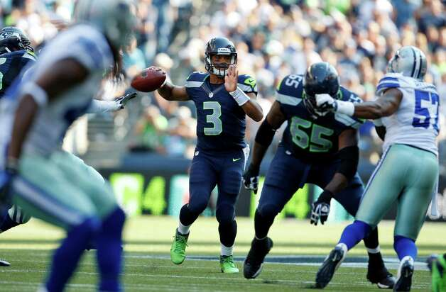 Seattle Seahawks quarterback Russell Wilson, center, looks to pass in the second half of an NFL football game against the Dallas Cowboys, Sunday, Sept. 16, 2012, in Seattle. (AP Photo/Kevin P. Casey) Photo: Kevin P. Casey, Associated Press / FR132181 AP