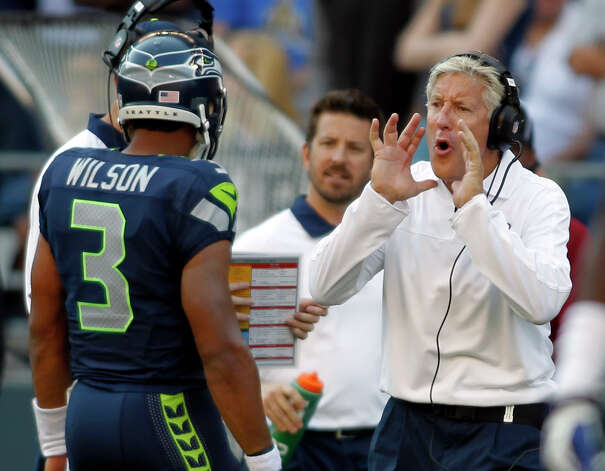 Seattle Seahawks head coach Pete Carroll, right, calls out to quarterback Russell Wilson (3) in the second half  of an NFL football game against the Dallas Cowboys, Sunday, Sept. 16, 2012, in Seattle. The Seahawks won 27-7. (AP Photo/John Froschauer) Photo: John Froschauer, Associated Press / FR74207 AP