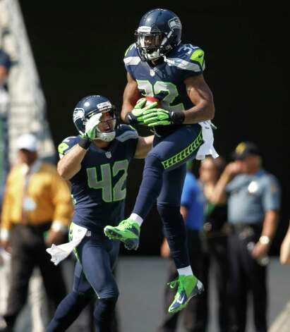 Seattle Seahawks' Jeron Johnson, right, celebrates his touchdown with Chris Maragos against the Dallas Cowboys in the first half of an NFL football game, Sunday, Sept. 16, 2012, in Seattle. (AP Photo/John Froschauer) Photo: John Froschauer, Associated Press / FR74207 AP