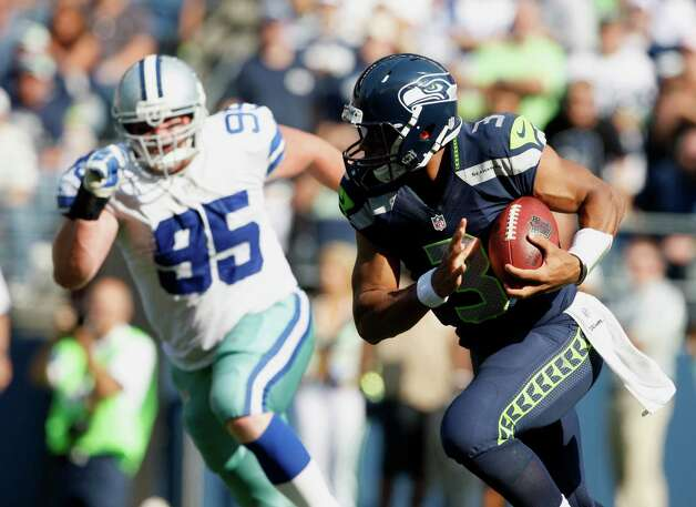 Dallas Cowboys' Kevin Ogletree, left, pursues  Seattle Seahawks' quarterback Russell Wilson, in the second half of an NFL football game, Sunday, Sept. 16, 2012, in Seattle. Seattle defeated Dallas 27-7.(AP Photo/Kevin P. Casey) Photo: Kevin P. Casey, Associated Press / FR132181 AP