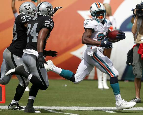 Reggie Bush leaves Michael Huff (24) and Tyvon Branch behind on his way to the end zone. Dolphins lineman Jake Long had recognized a vulnerability in the Raiders' defense on blitzes by Branch. Photo: Wilfredo Lee, Associated Press