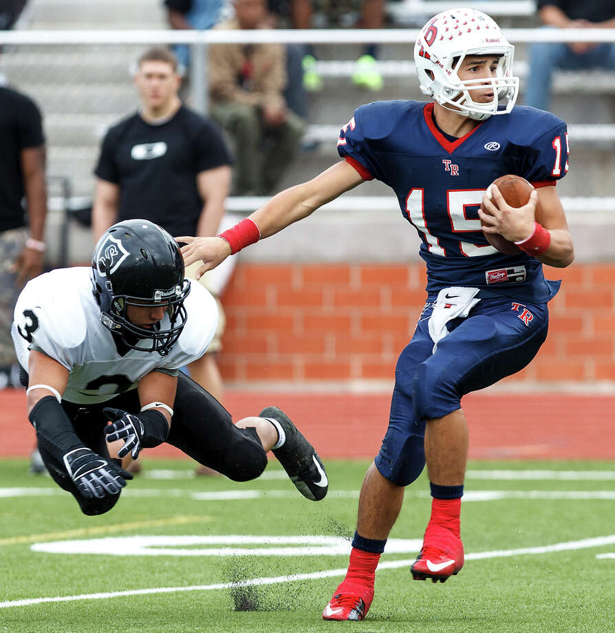 Charger quarterback Kyle Poeske is pressured to make a bad throw by Michael Huron (49) and Troy Irby as Champion hosts Brennan in 4A first round playoff action at Boerne Stadium on November 16, 2012. Photo: MARVIN PFEIFFER, Marvin Pfeiffer/ Express-News / Express-News 2012