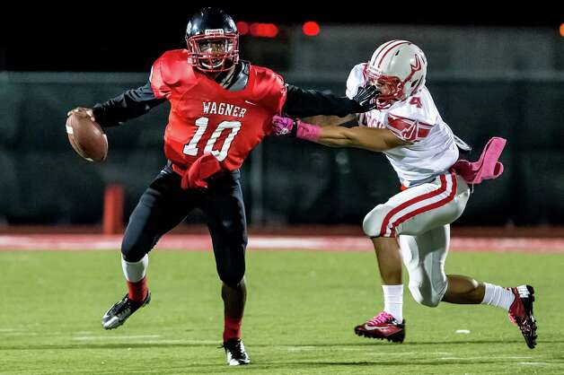 "Wagner quarterback Tekoa Bryant-Mckinnies tries to elude the grasp of Judson's Malik Pryor during the first quarter of theirgame at Rutledge Stadium on Oct. 12, 2012.  Judson won the ""Hammer Bowl"" 30-0.  MARVIN PFEIFFER/ mpfeiffer@express-news.net Photo: Kin Man Hui, San Antonio Express-News / © 2012 San Antonio Express-News"
