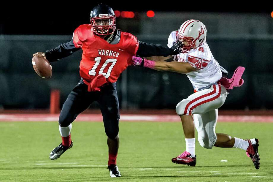 Wagner's Jaroyce Bratcher-Molett (33) finds room to run against Madison's Daniel Ortega (60) and Derek Machen (55) in the Class 5A District I playoff game in the first half at Rutledge Stadium on Friday, Nov. 16, 2012. Photo: MARVIN PFEIFFER, Marvin Pfeiffer/ Express-News / Express-News 2012