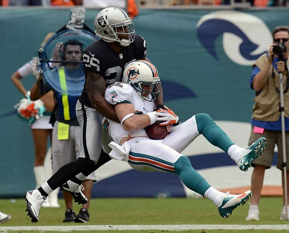 Oakland's Pat Lee brings down Miami's Brian Hartline after one of his career-best nine catches. Lee was making his first start for the Raiders in place of the injured Ron Bartell. Photo: Rhona Wise, Associated Press