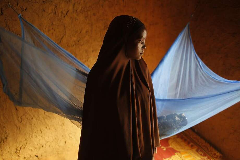 Zali Idy, 12, poses in her bedroom in the remote village of Hawkantaki, Niger. Zali was married in 2011. In January 2012, soon after she turned 12, she was carried on a bullock cart to her 23-year-old husband's home. Even during the best of times, one out of every three girls in Niger marries before her 15th birthday, a rate of child marriage among the highest in the world, according to a UNICEF survey. Now this custom is being layered on top of a crisis. At times of severe drought, parents pushed to the wall by poverty and hunger are marrying their daughters at even younger ages. A girl married off is one less mouth to feed, and the dowry money she brings in goes to feed others. (AP Photo/Jerome Delay) PART OF A 15-PICTURE PACKAGE BY JEROME DELAY Photo: Jerome Delay, Associated Press