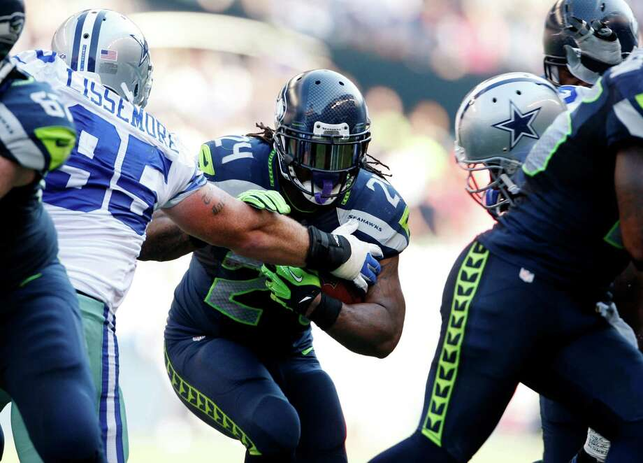 CORRECTS TO RUNS FOR YARDAGE NOT SCORES - Seattle Seahawks' Marshawn Lynch (24) pushes aside Dallas Cowboys' Sean Lissemore as he runs for yardage in the second half of an NFL football game of Sunday, Sept. 16, 2012, in Seattle. Photo: AP