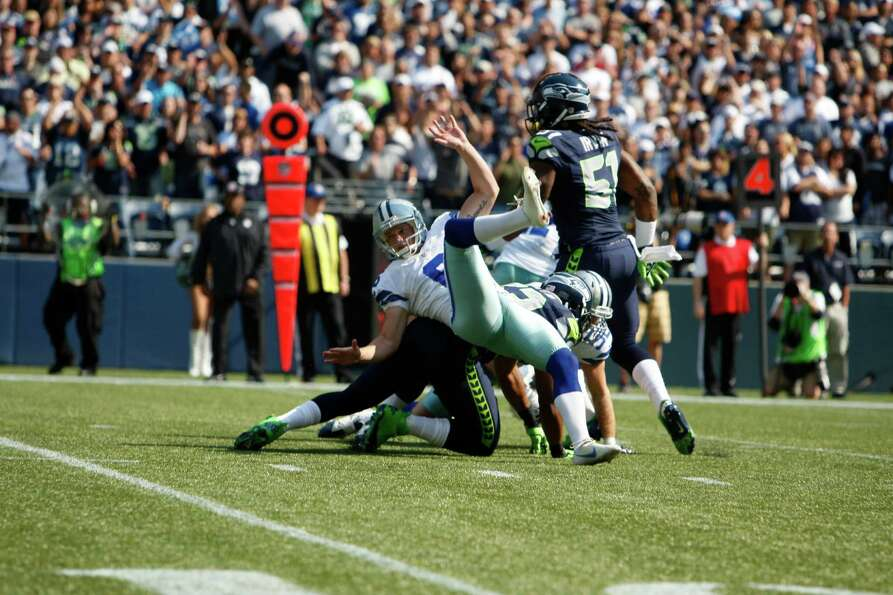 Dallas Cowboys' Chris Jones, left, has his kick blocked by the Seattle Seahawks in the first half of