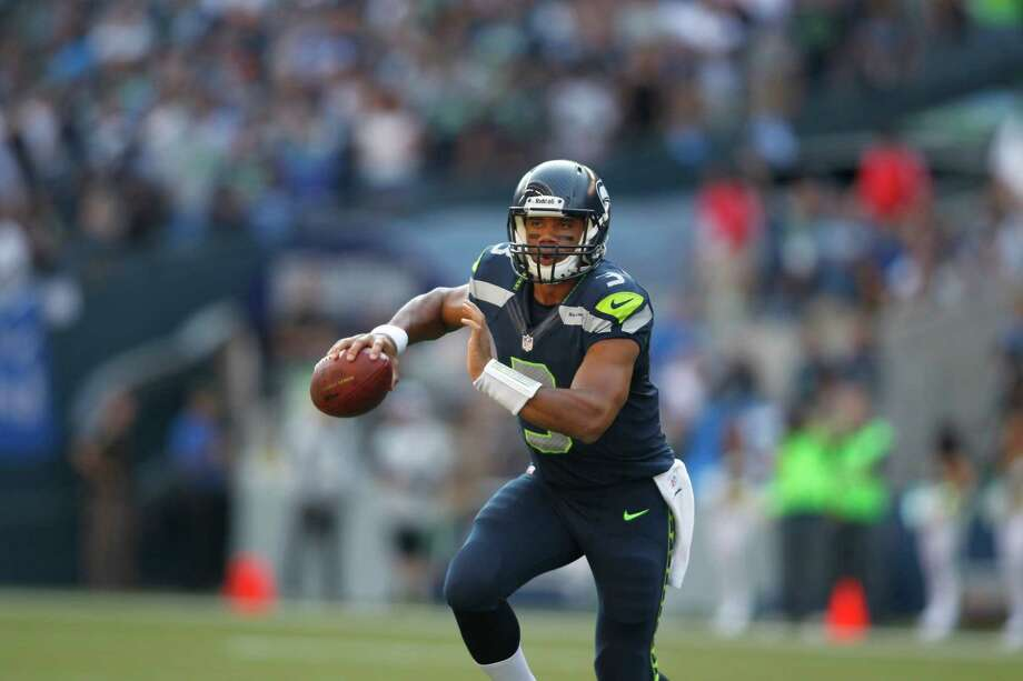 Seattle Seahawks quarterback Russell Wilson rolls out to look for an open reciever against the Dallas Cowboys in the second half of an NFL football game, Sunday, Sept. 16, 2012, in Seattle. Photo: AP