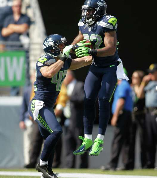 Seattle Seahawks' Jeron Johnson, right, celebrates his touchdown with Chris Maragos against the Dall