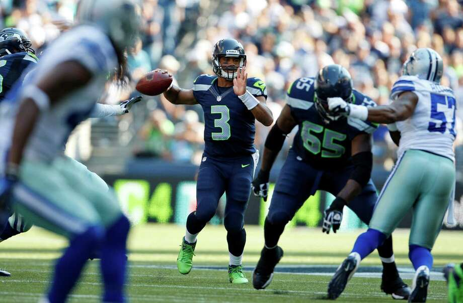 Seattle Seahawks quarterback Russell Wilson, center, looks to pass in the second half of an NFL football game against the Dallas Cowboys, Sunday, Sept. 16, 2012, in Seattle. Photo: AP