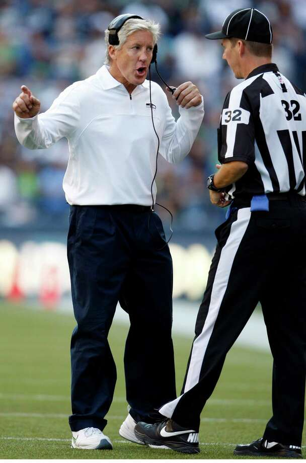 Seattle Seahawks head coach Pete Carroll, left, talks with back judge Mike Fischer during the second half of an NFL football game against the Dallas Cowboys, Sunday, Sept. 16, 2012, in Seattle. Photo: AP