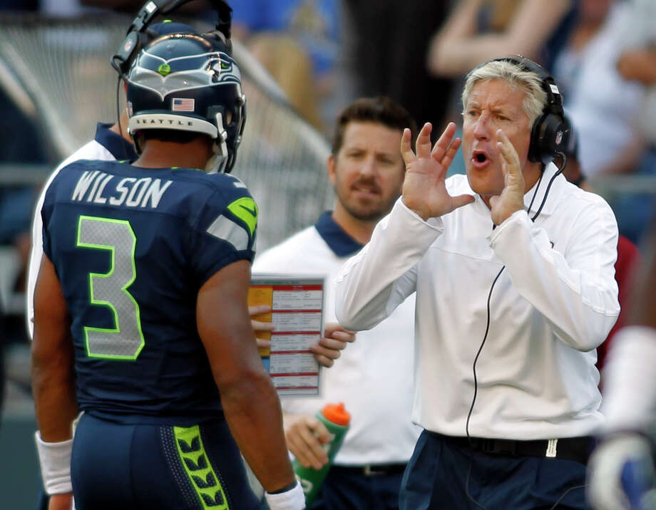 Seattle Seahawks head coach Pete Carroll, right, calls out to quarterback Russell Wilson (3) in the second half  of an NFL football game against the Dallas Cowboys, Sunday, Sept. 16, 2012, in Seattle. The Seahawks won 27-7. Photo: AP