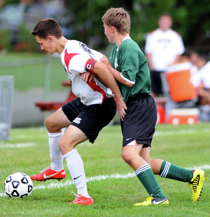 Academy's Jordan Newton (19), left, battles for the ball during their soccer game against Ravena on Saturday, Sept. 15, 2012, at Albany Academy in Albany, N.Y. (Cindy Schultz / Times Union) Photo: Cindy Schultz / 00019241A