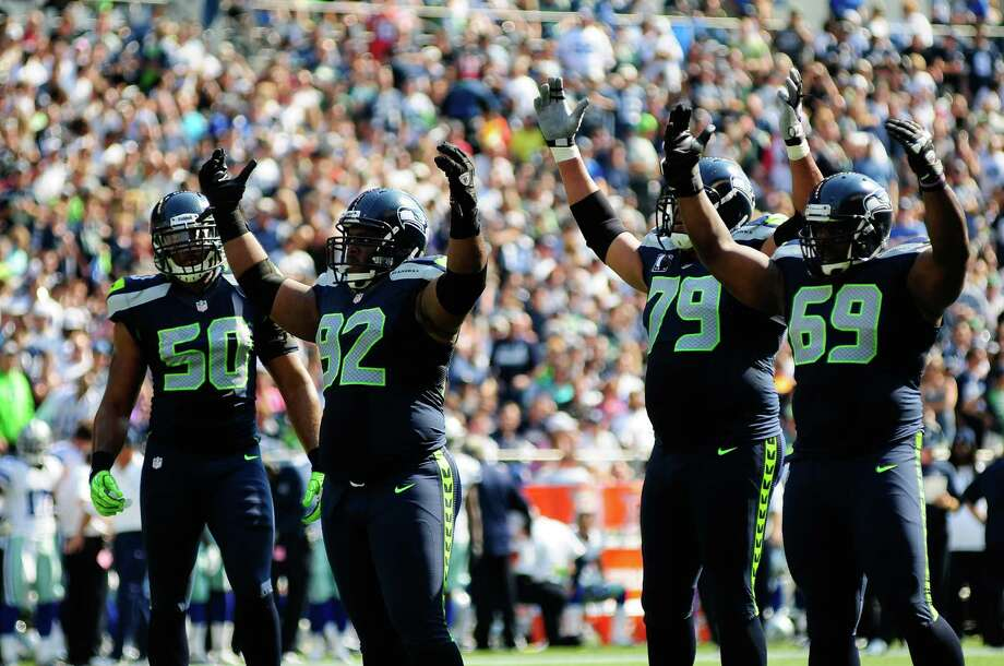 A group of Seahawks raise their arms to hype up the crowd during the 2nd half of the Seahawks vs Cowboys game at CenturyLink Field on Sunday, September 16, 2012. The Seahawks, playing to a crowd of 68,000, won easily with a score of 7-27. Photo: LINDSEY WASSON / SEATTLEPI.COM