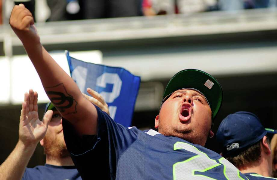 A fan raises his fist and cheers the Seahawks on as they prepare to execute a play during the Seahawks vs Cowboys game at CenturyLink Field on Sunday, September 16, 2012. The Seahawks, playing to a crowd of 68,000, won easily with a score of 7-27. Photo: LINDSEY WASSON / SEATTLEPI.COM