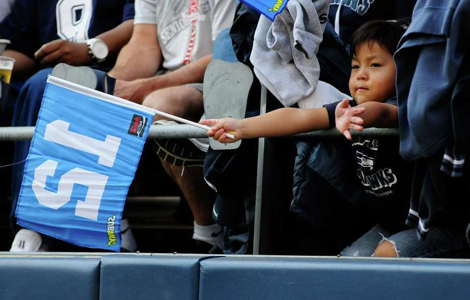 Micholeone Recabarren, 3, waves a 12th man flag while watching the Seahawks vs Cowboys game at CenturyLink Field on Sunday, September 16, 2012. The Seahawks, playing to a crowd of 68,000, won easily with a score of 7-27. Photo: LINDSEY WASSON / SEATTLEPI.COM