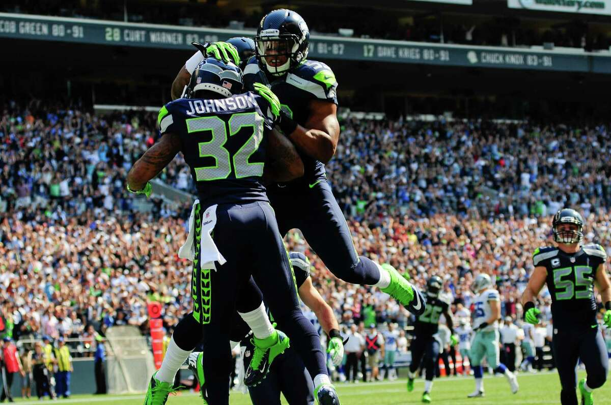 Other players celebrate Jeron Johnson's touchdown for the Seahawks, bringing the score to 0-10, during the Seahawks vs Cowboys game at CenturyLink Field on Sunday, September 16, 2012. The Seahawks, playing to a crowd of 68,000, won easily with a score of 7-27.