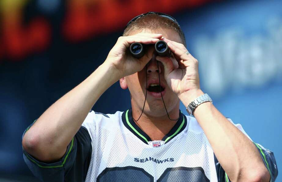 Joe Lindquist looks through a set of binoculars during the Seahawks vs Cowboys game at CenturyLink F