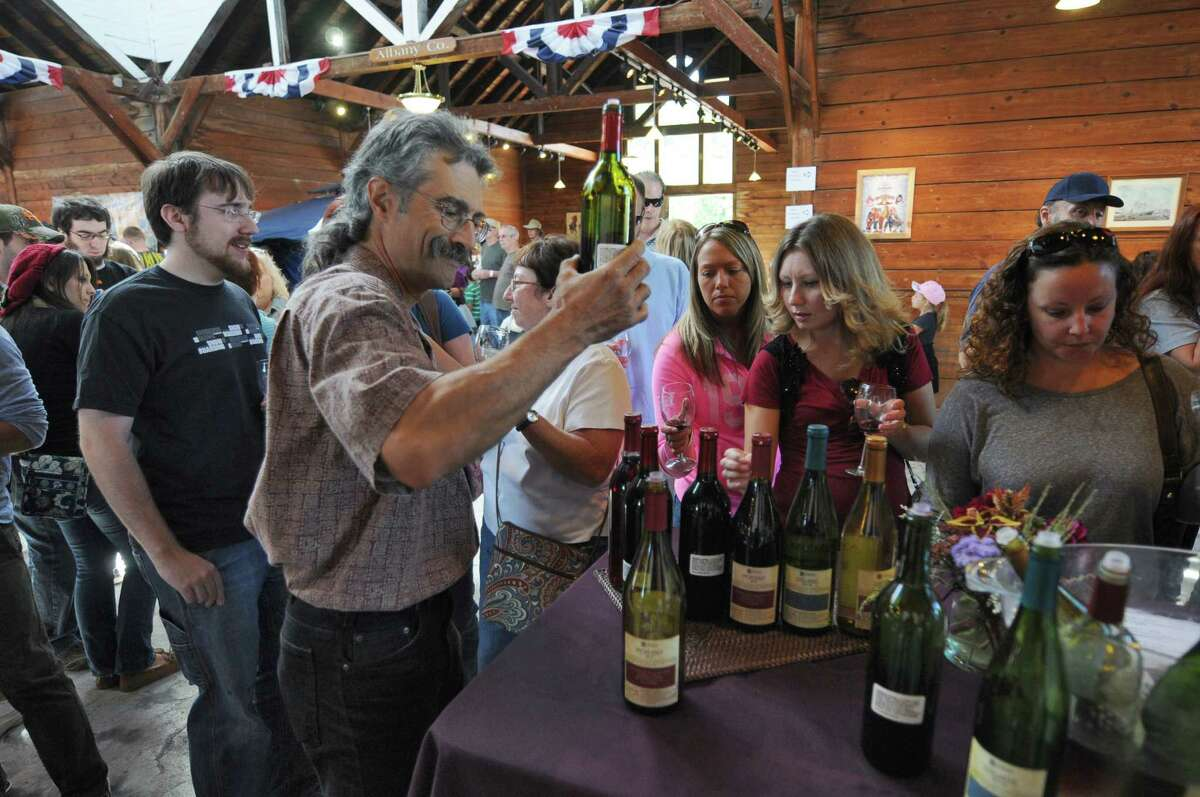 Greg Giorgio of Altamont Vineyard and Winery, left, pours samples of their wines for visitors to the 20th annual Capital Region Apple & Wine Festival at the Altamont Fairgrounds, on Sunday Sept. 16, 2012 in Altamont, NY. (Philip Kamrass / Times Union)
