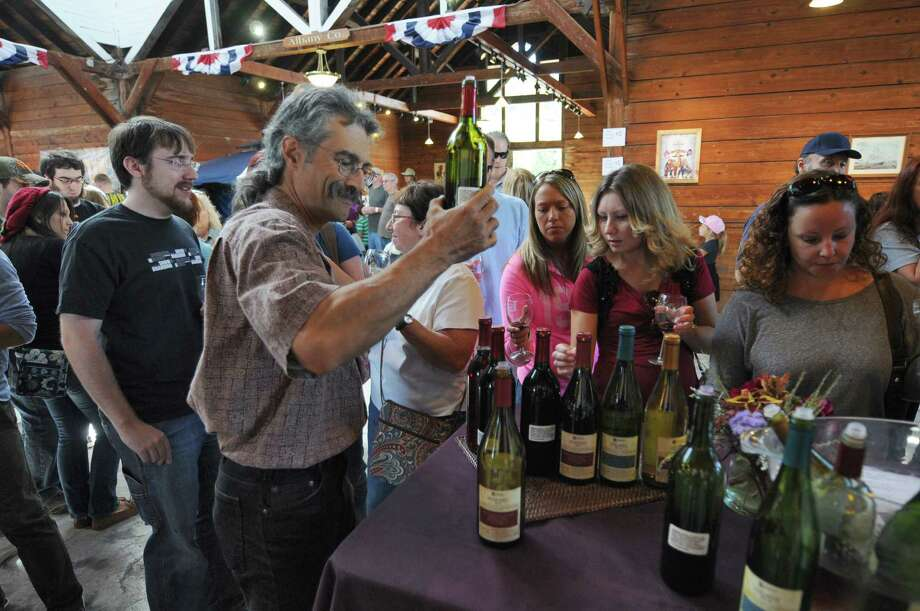 Greg Giorgio of Altamont Vineyard and Winery, left, pours samples of their wines for visitors to the 20th annual Capital Region Apple & Wine Festival at the Altamont Fairgrounds, on Sunday Sept. 16, 2012 in Altamont, NY.   (Philip Kamrass / Times Union) Photo: Philip Kamrass / 00019231A