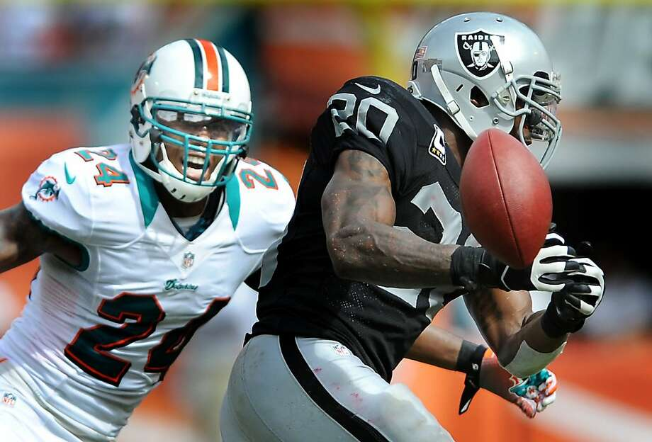 Miami's Sean Smith chases Oakland's Darren McFadden as McFadden cannot handle a short pass in the fourth quarter. The Miami Dolphins defeated the Oakland Raiders, 35-13, at Sun Life Stadium in Miami Gardens, Florida, on Sunday, September 16, 2012. (Robert Duyos/Sun Sentinel/MCT) Photo: Robert Duyos, McClatchy-Tribune News Service