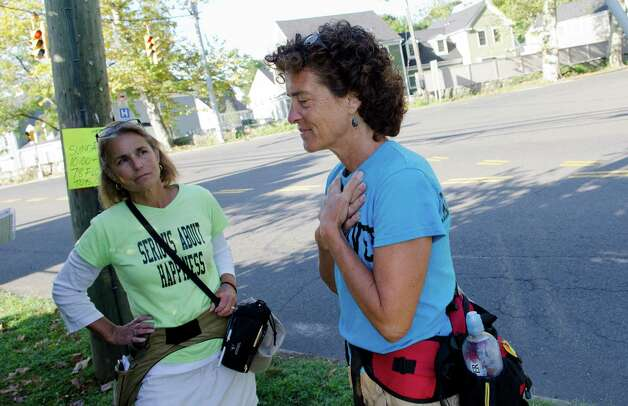 Paula Francis, 54, look on as Linda Wheatley, 53, of Montpelier, VT, touches her hands to her heart as she reflects on the purpose of the Happiness Walk as they pause briefly along Stillwater Avenue in Stamford on Sunday, Sept. 16, 2012. Francis and Wheatley left Stowe, Vermont on August 25, 2012 on a 560-mile, 44-day walk to Washington, D.C. to raise awareness about the need to adopt happiness and well-being as the ultimate goal of social and political policy. Photo: Amy Mortensen / Connecticut Post Freelance